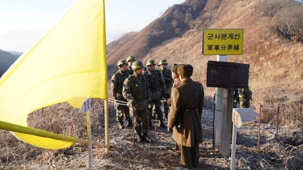 North and South Korean soldiers approaching each other at the inter-Korean border