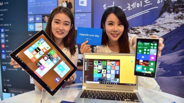 Dos mujeres muestran el sistema Windows en diferentes dispositivos