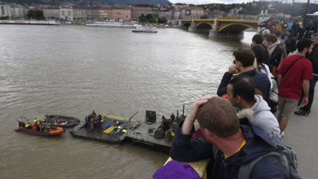 People on Margaret Bridge watch operations to prepare the recovery of the capsized boat in Budapest
