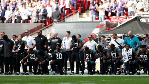 ロンドンで行われた試合で、国歌演奏中に膝をつくジャクソンビル・ジャガーズの選手たちと、その後ろで腕を組むコーチたち(24日)