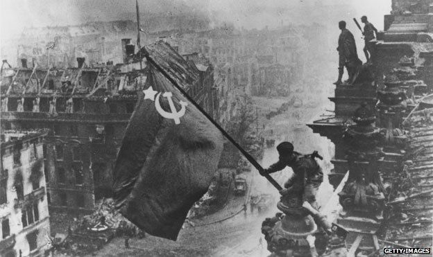 Red Army soldier raises the Soviet flag over the Reichstag in Berlin