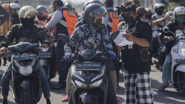 Anggota satuan pengamanan adat Bali atau Pecalang memeriksa surat jalan seorang pengendara saat hari pertama penerapan Pembatasan Kegiatan Masyarakat (PKM) di pos pantau perbatasan Biaung, Denpasar, Bali, Jumat (15/05).