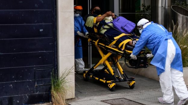Enfermeros llevan a un paciente con covid-19