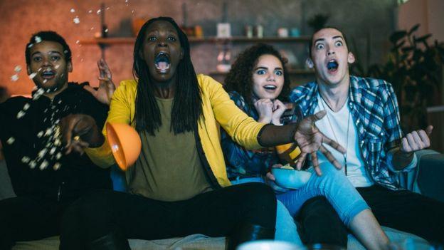 Grupo de amigos viendo película de horror y saltando