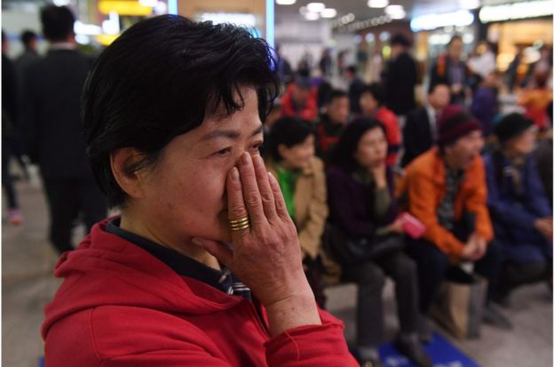 "A woman who opposes South Korean President Moon Jae-in watches news footage of Moon and North Korean leader Kim Jong Un meeting in the Demilitarized Zone, at a railway station in Seoul on April 27, 2018. The leader of nuclear-armed North Korea Kim Jong Un and the South""s President Moon Jae-in said they were committed to the denuclearisation of the Korean peninsula after a historic summit on April 27. / AFP PHOTO / GREG BAKERGREG BAKER/AFP/Getty Images"