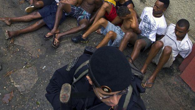 Un grupo de hombres siendo detenidos por un policía.