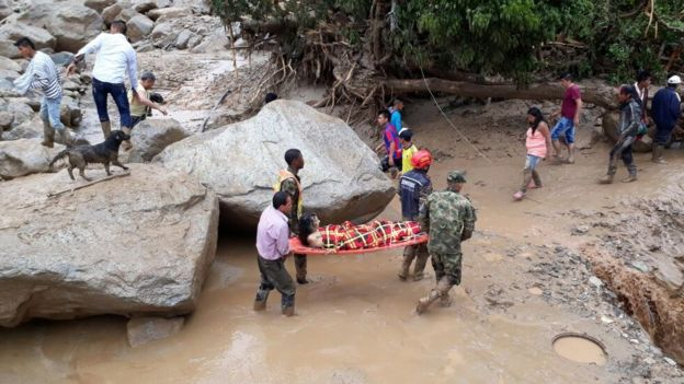 Soldados rescatan a una mujer en una camilla.