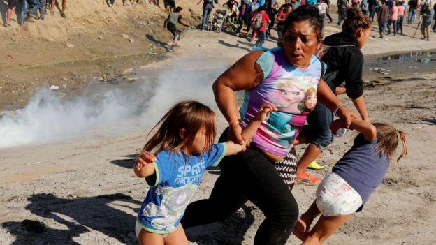 Una mujer huye de gases lacrimógenos junto a sus dos hijas en la frontera entre EE.UU. y México en noviembre de 2018