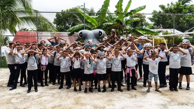 Niños con máscaras de tiburón y un tiburón inflable de juguete gigante