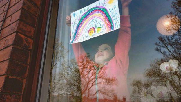 Una niña cuelga un arcoíris dibujado en la ventana.