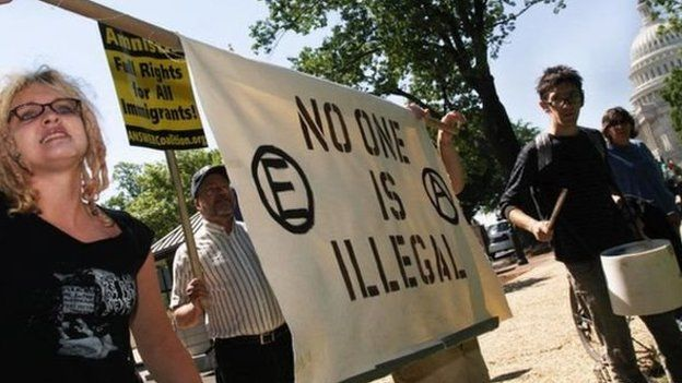 Protesters holding a sign reading 'no one is illegal'