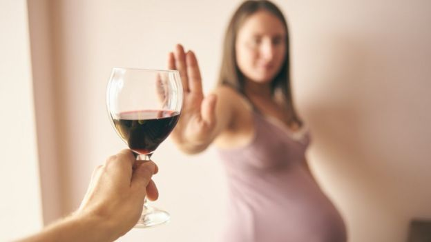 Una mujer embarazada rechaza una copa de vino.