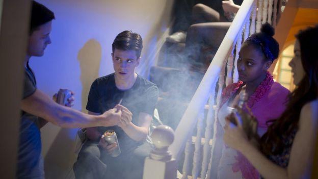 Adolescentes bebiendo y fumanod en una fiesta en una casa