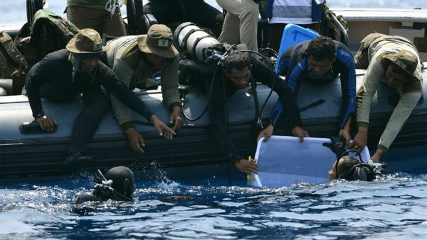 """Indonesian Navy diver (bottom L) holding a recovered """"black box"""" under water before putting it into a plastic container (R)"""