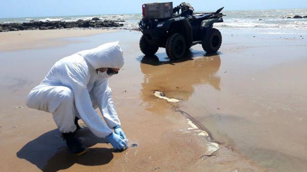 Biólogo colhe amostra de petróleo em praia no Rio Grande do Norte