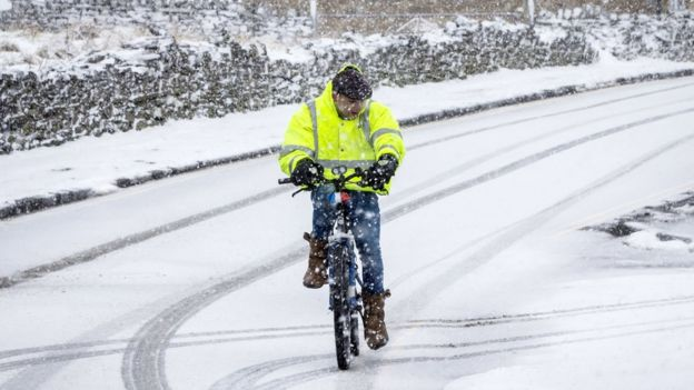 A man rides a bike in snowy conditions in Hawes in the Yorkshire Dales National Park