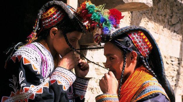 Geleneksel kıyafetleriyle Kalaş kızlar birbirinin örgülerini öpüyor