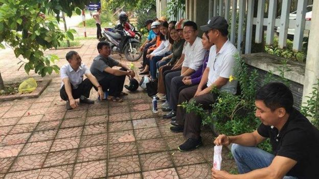 Người thân và ủng hộ ông Trực ngồi gần cổng tòa án. Luật sư Nguyễn Văn Miếng cho biết có rất nhiều công an trong và bên ngoài phiên tòa