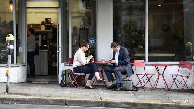 Duas pessoas tomam café em mesa colocada na calçada