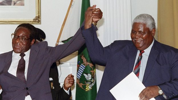 Zimbabwe's President Robert Mugabe (left) and Joshua Nkomo raise their fists (22 December 1987)