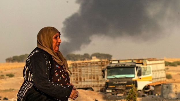 A woman walks as smoke billows following Turkish bombardment in Syria's town of Ras al-Ain