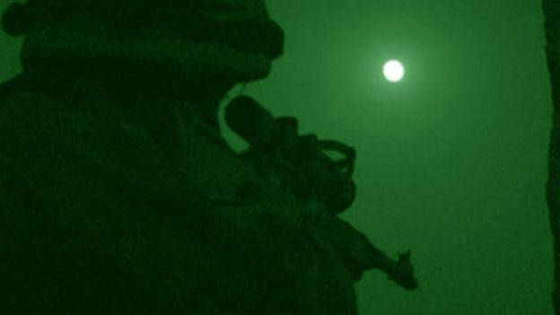 A soldier takes aim at night in Afghanistan.
