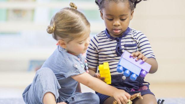 Los niños pequeños están sentados en el piso jugando con bloques de construcción de juguetes
