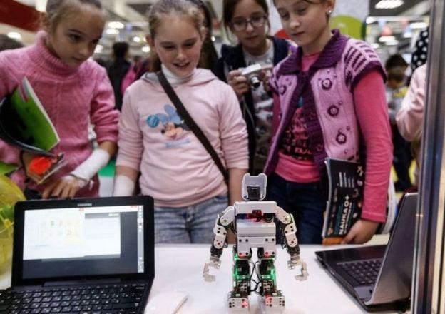 Niñas rusas observando un robot.