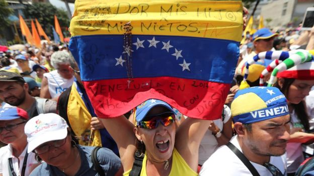 Mujer simpatizante de Guaidó con una bandera de Venezuela