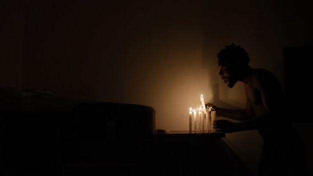Chadrac Kembilu Nkusu acende velas durante um apagão na favela Cinco Bocas