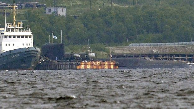 A rescue tugboat (L) and the BS-136 Orenburg ballistic missile submarine (R) carrying a nuclear deepwater station of Project 10831 at the Russian Northern Fleet's base