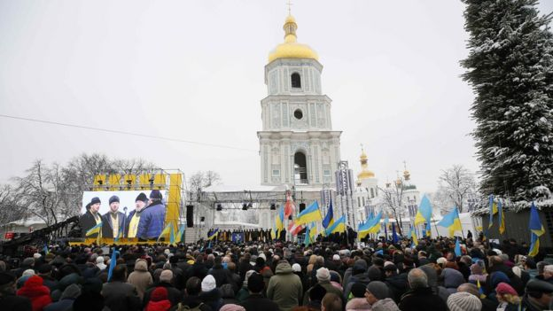 Ukrainians gather outside Saint Sophia's Cathedral bell tower in Kiev