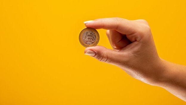 Mulher segura uma moeda de um real