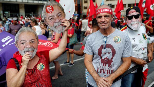Manifestantes com máscara do Lula em protesto