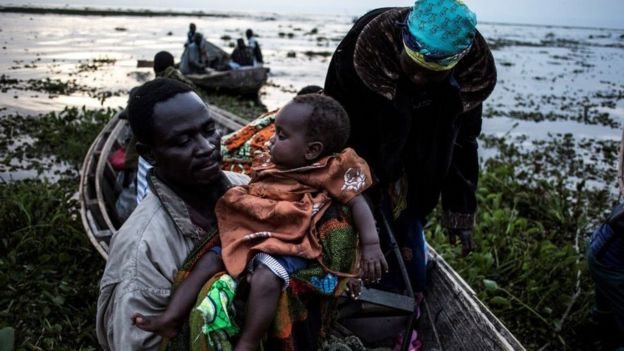 Internally displaced Congolese return to the shore line of lake Albert after spending the night out in the lake for safety on March 05, 2018 in Tchomia.