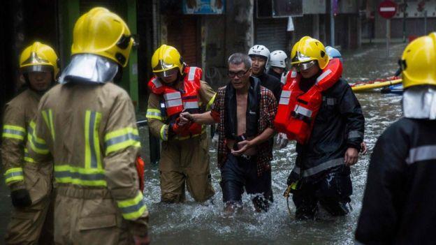 救援人員協助澳門居民涉水撒離。