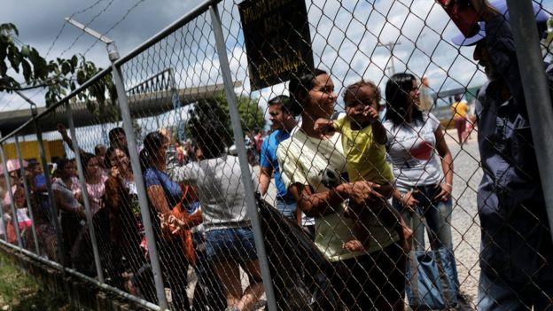 Imigrantes venezuelanos fazem fila para apresentar passaporte e entrar no Brasil.