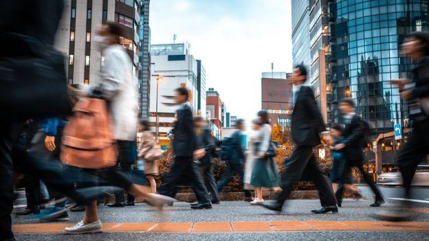 Multitud de gente desenfocada caminando.