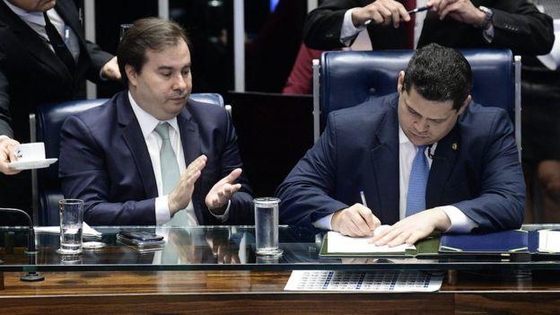 No Congresso, Rodrigo Maia e Davi Alcolumbre aparecem sentados à mesa - o primeiro batendo palmas e o segundo, assinando papel