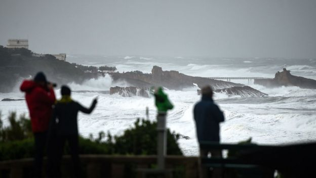 People look at the ocean;s waves hitting the coast in Biarritz, south-western France, on 03 November, 2019.