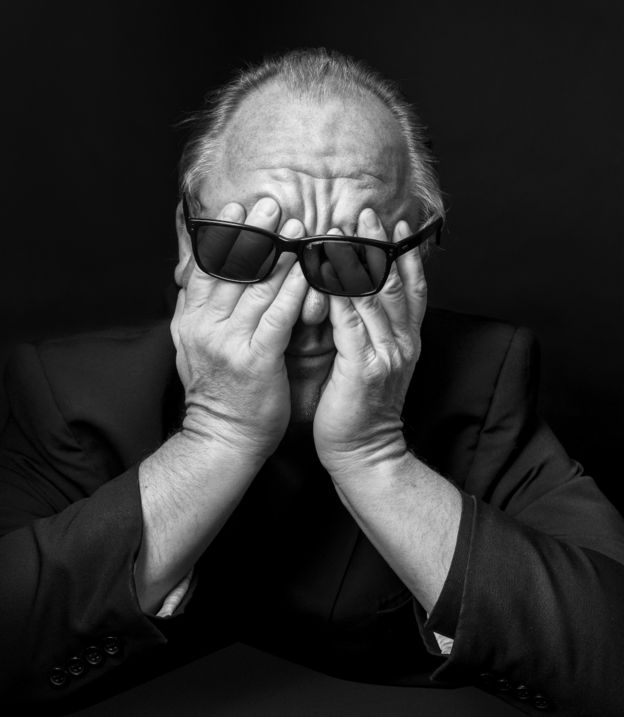 رجل يخفي عينيه بأصابع يديه من وراء نظارة سوداء