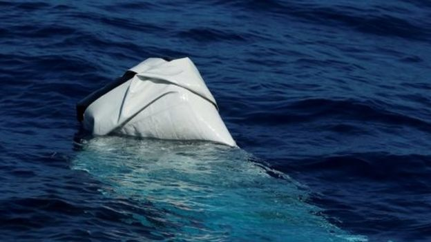 A deflated and half-sunken rubber dinghy of the sort used by migrants is seen from the Migrant Offshore Aid Station (MOAS) ship Phoenix in international waters in the central Mediterranean off the coast of Tripoli i(13 April 2017)