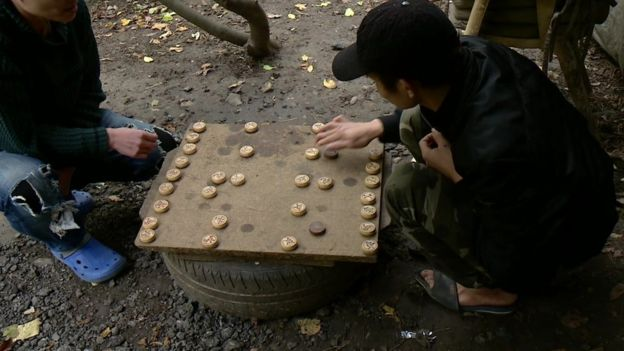 Two men play a game as they wait at the camp