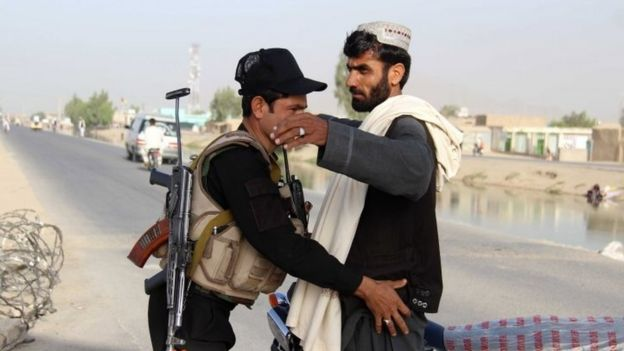 An Afghan security official frisks a ma in Kandahar (26 May 2017)