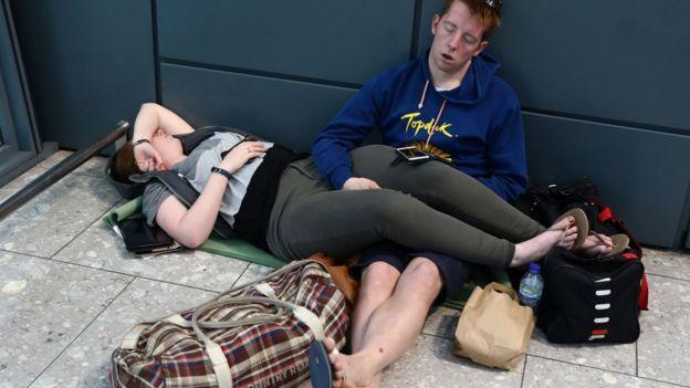 People sleep next to their luggage at Heathrow Terminal 5 in London