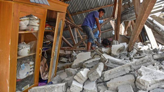 Un aldeano busca entre los escombros de una casa destruida por el terremoto en Lombok, Indonesia, julio 29, 2018