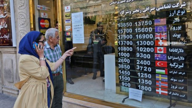People walk past a foreign exchange shop in Tehran, Iran (22 April 2019)