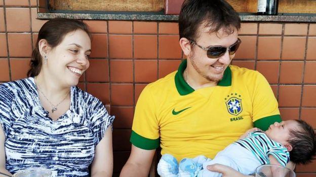 Mariana Franco e Juliano Lustosa sorriem olhando para o bebê Davi