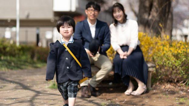 Una niña japonesa se dirige a la escuela mientras sus padres la observan