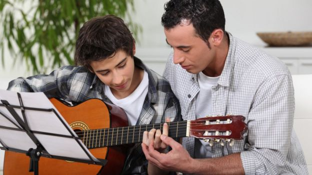 A Bark guitar teacher helping a boy to learn the instrument